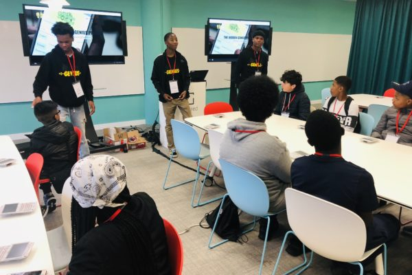 Hidden Genius Alumni Youth Educators lead a tech workshop to students of color from London.